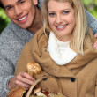 Young couple gathering mushrooms and chestnuts — Stock Photo