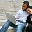 Couple sitting on some steps with a laptop — Stock Photo #8535447