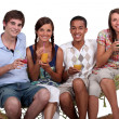 A bunch of friends enjoying cocktails on a hammock. — Stock Photo #8535537