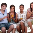 A bunch of friends enjoying cocktails on a hammock. — Stock Photo
