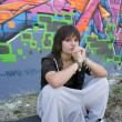 Portrait of a girl sitting on a skateboard in front of a wall of graffiti — Stock Photo #8535855