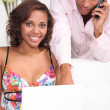 Black woman doing computer and his boyfriend at phone — Stock Photo