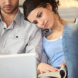 Couple with laptop and book — Stock Photo