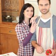 Smiling man and woman standing in kitchen — Stockfoto