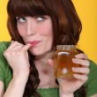Stock Photo: Playful womeating honey