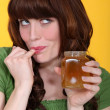 Playful woman eating honey — Stock Photo