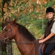 Young woman riding a horse through woodland — Stok fotoğraf