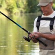 Mature gentleman fishing in river — Stock Photo
