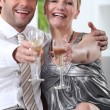 Couple sat down holding champagne glasses arms held out — Stock Photo