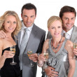 Double date: couples in party dress drinking champagne — Stok fotoğraf