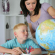 Stock Photo: Woman giving her son a geography lesson