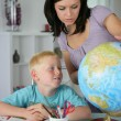 Stock Photo: Womgiving her son geography lesson
