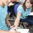Teenage girl looking at her classmate's answers — Stock Photo #8538603
