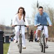 Young couple riding bikes along a boardwalk — Stock Photo