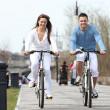 Young couple riding bikes along a boardwalk — Stock Photo