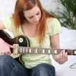 Girl playing guitar sat on a bed — Stock Photo #8538821