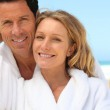 Happy couple wearing dressing gowns at the beach — Stock Photo #8538848