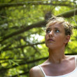 Woman stood amongst branches - Stock Photo