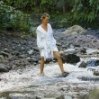 Woman walking in a river - ストック写真