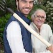 Senior with gardener and fork — Stockfoto