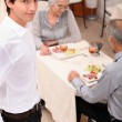 An old couple eating at restaurant and a young waiter - Stock Photo