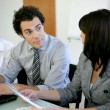Stock Photo: Worker explaining document to colleague