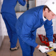 Stock Photo: Plumbers working in tiled room