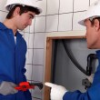 Plumber and his apprentice working together — Stock Photo