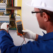 An electrician checking the energy meter. — Stock Photo