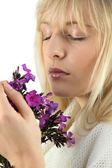 Close-up shot of blonde eyes shut smelling bunch of flowers — Stock Photo