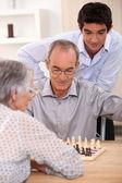 Jovem assistindo um casal mais velho a jogar xadrez — Foto Stock