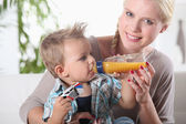 Portrait of a woman feeding her son — Stock Photo