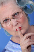 Elderly woman with her hair in rollers holding her finger up to her lips — Stock Photo