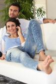 Couple on sofa telephoning — Stock Photo