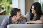 Flirtatious couple sat on sofa — Stock Photo