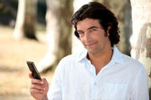 Man sending a text message in the forest — Stock Photo
