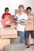 Three lads packing up and moving home — Stock Photo
