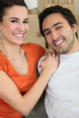 Young couple all smiles moving flats — Stock Photo