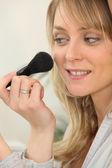 Young woman applying blusher — Stock Photo
