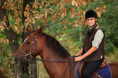 Young woman riding a horse through woodland — Foto Stock