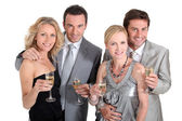 Double date: couples in party dress drinking champagne — Stock Photo