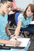 Teenage girl looking at her classmate's answers — Stock Photo