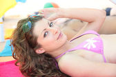 Teenage girl lying on the beach — Stockfoto