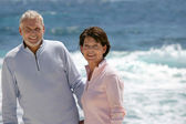 Elderly couple enjoying stroll on the beach — Stock Photo