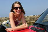 Smiling woman leaning on a car — Stok fotoğraf