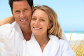 Happy couple wearing dressing gowns at the beach — Stock Photo