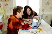 Woman helping grandmother with computer — Stock Photo