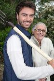Senior with gardener and fork — Stock Photo
