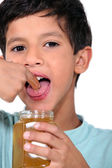Boy tasting some honey — Stock Photo