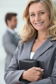 Smiling businesswoman holding personal organiser with colleague in backgrou — Stock Photo